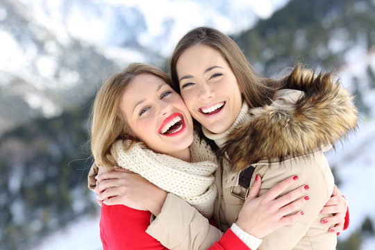 Happy friends cuddling and posing in winter holiday