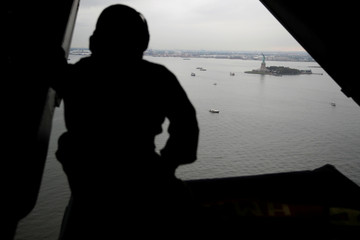 A United States Marine looks out the back of a V-22 Osprey helicopter transporting members of the press as it passes over the Statue of Liberty in New York Harbor