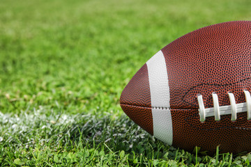 Ball for American football on fresh green field grass, closeup. Space for text