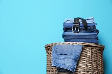Stack of different jeans on basket against color wall with space for text