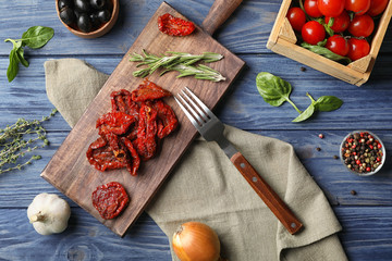 Flat lay composition with dried tomatoes on wooden table