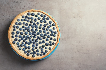 Tasty blueberry cake on gray background, top view with space for text