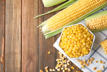 Flat lay composition with corn kernels on wooden background. Space for text