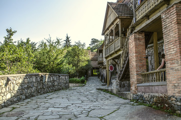 Narrow alley with old houses made of rough stone and brick columns,with wooden carved balconies in the Museum Tufenkian Old Dilijan