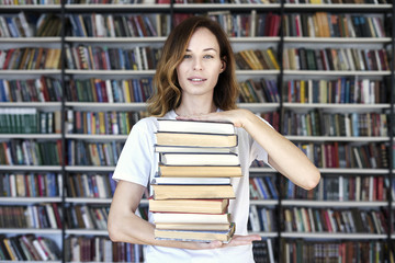 Woman model college student with books at library holds bunch of books, looks smart, smiling to camera. bookshelves at the library. Knowledge and self-development