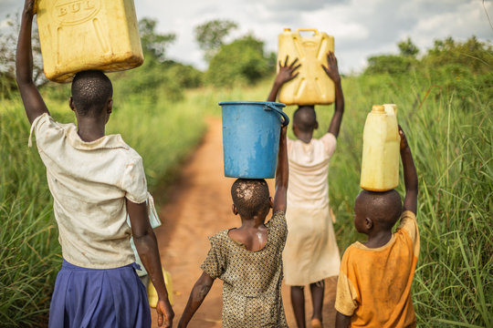 Group of young African kids walking with buckets and jerrycans on their head as they prepare to bring clean water back to their village.