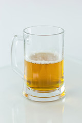 Beer glass half full on white background