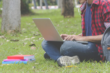 Asian attractive male student thinking about coursework strategy sitting in university garden with laptop computer connected to wireless internet.