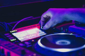 Dj man mixing song on the stage at the club. Close up on hand