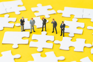 Company management teamwork find out solutions to solve problem concept, miniature people businessmen organization leader, staffs or employee help finishing jigsaw puzzle pieces on yellow background