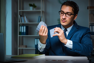 Young business playing cards late in office