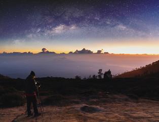 Traveller taking photograph of landscape sunrise and sky full of stars in dawn