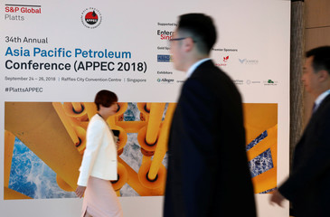 People pass a signage of the 34th Asia Pacific Petroleum Conference (APPEC) in Singapore