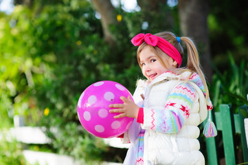 Cute little fashion girl playing with ball outdoor