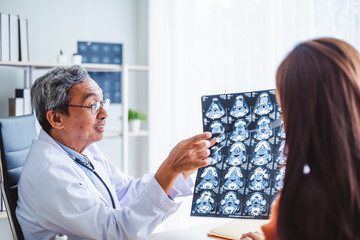 Asian doctors show diagnose patient x-ray  radiography film to old patient, asian medical concept