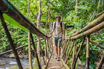 Male traveler on the suspension bridge in Bali