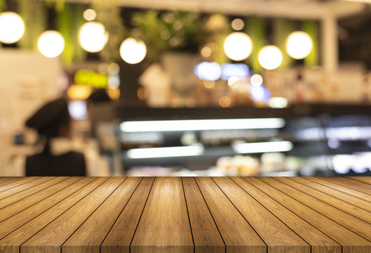 Wooden board empty table and blurred or defocus background and light bulb bokeh . Perspective brown wood table over blur in bakery shop background , this image in coffee shop and bakery shop concept