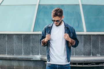 A stylish man with a beard in glasses with a white T-shirt. Street photo