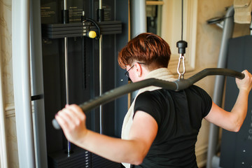 redhead adult woman with short haircut execute exercise with exercise-machine in gym