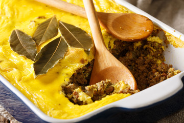 Bobotie hearty South African dish made primarily of curried minced meat topped with milk and egg mixture and baked close-up. horizontal