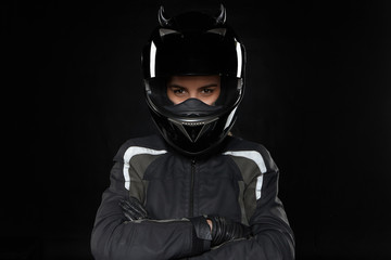 Motorcycle sports, extreme, competition and adrenaline. Active young female racer wearing protective helmet and uniform going to participate in road racing or motorcross, crossing arms on her chest Wall mural