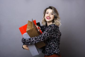 Young woman hugging shopping bags
