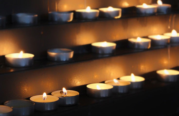 Many beautiful lit tealight candles glowing with a golden yellow light - selective focus.Concept of faith and peace, remembering the dead