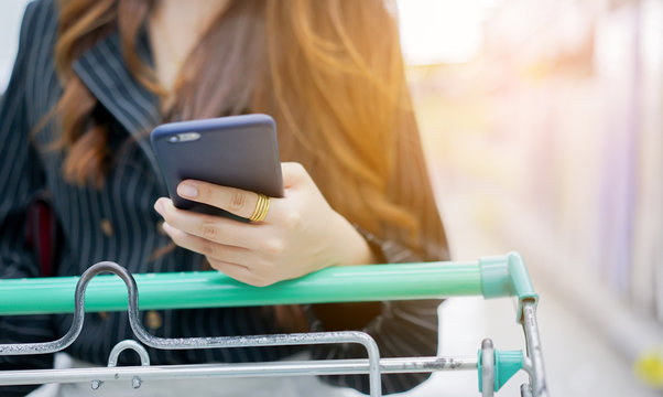 close up housewife holding smartphone for checklist at supermarket , life concept