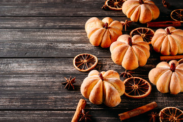 Homemade cakes in the shape of pumpkin on wooden background with copy space