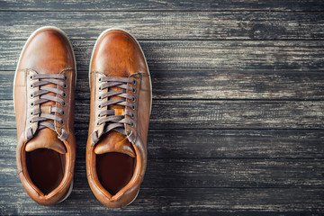 Brown leather men's boots on wooden background top view with copy space