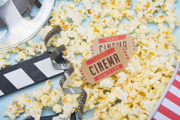 scattered popcorn on a blue background, a film and two tickets