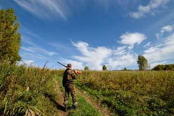 The hunter is on his way to the field. Autumn, clear sky and sun.
