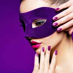 Portrait of a pretty woman with purple nails and violet theatre mask on face.