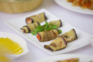 A dish of toppings, wrapped in fried eggplant.