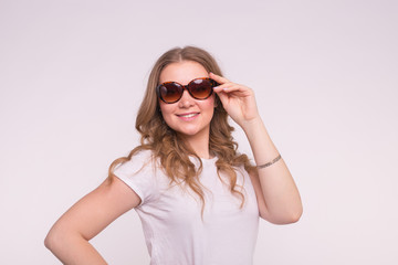 Beautiful white curly young woman wearing white t-shirt and sunglasses on white background