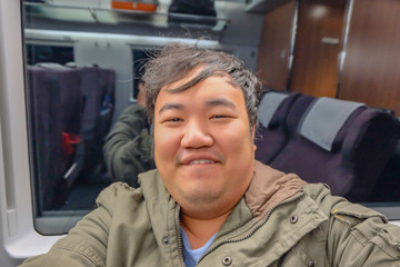 Asian Fat traveler selfie himself on the high speed train from yiwu city to shanghai city in china