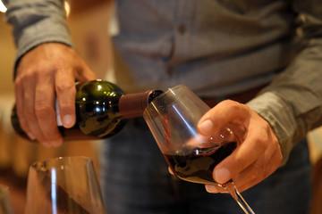Man serving red wine for tasting in winery