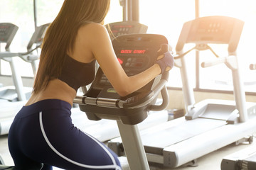 Woman Exercise bike cardio workout at fitness gym taking weight loss with machine aerobic for slim and firm healthy in the morning.