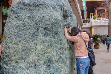 Shanghai/China -  January 25 2015: People touch the Big spirit stone in jian an temple shanghai city china