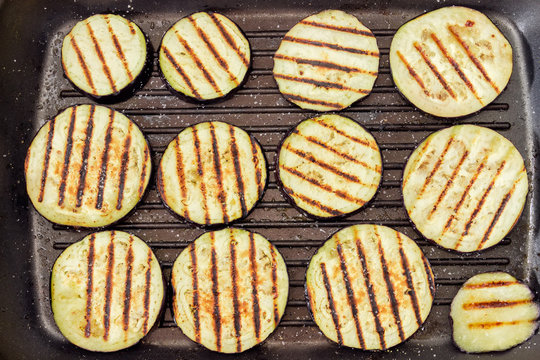 Background of grilled chopped by circles eggplants on grill pan