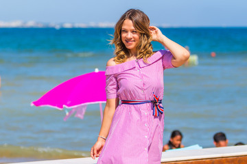 Young beautiful blonde hair curvy model posing on the beach wearing pink striped dress - oversize model with curly long hair is on seaside looking into camera - summer colourful (colorful) image