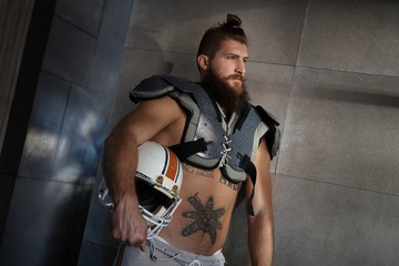Dedicated american football player holding helmet