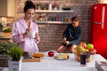 Couple having breakfast drinks in kitchen