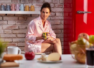 Young woman drinks breakfast coffee in pyjama