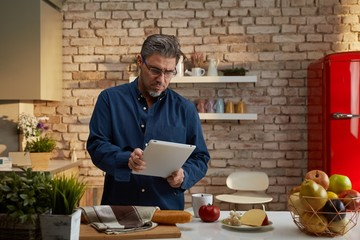Older man having breakfast in kitchen