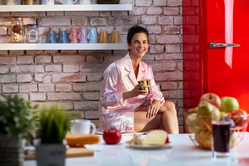 Happy woman laughing drinking breakfast coffee