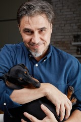 Man loving cute dachshund puppy