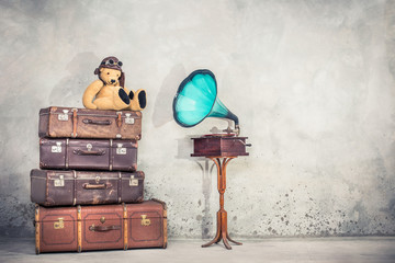 Teddy Bear toy with leather aviator's hat and goggles sitting on retro old aged classic travel suitcases and aged phonograph turntable. Listening music concept. Vintage instagram style filtered photo