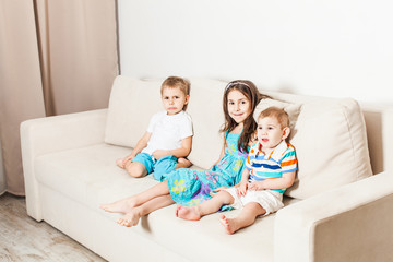 Sister and two brothers are sitting on a light sofa.