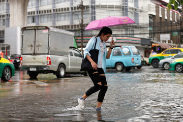 A woman walks on a flooded street in Bangkok